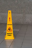 Caution wet floor sign on tiled floor. With stone wall on background Stock Images