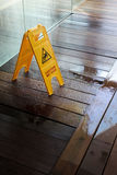 Caution wet floor sign. Vertical shot of a yellow caution wet floor sign on wooden floor of a wellness center Royalty Free Stock Photos
