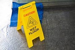 Caution wet floor warning sign. On floor background Stock Photos