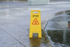 Caution wet floor warning sign near wet area. With blurred background Royalty Free Stock Images