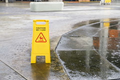 Caution wet floor warning sign near wet area. With blurred background Stock Photos