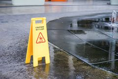 Caution wet floor warning sign near wet area. With blurred background Royalty Free Stock Photography
