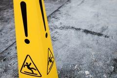 Caution wet floor, yellow warning sign fragment. Caution wet floor, yellow warning sign stands on gray asphalt urban ground, closeup photo Royalty Free Stock Photography