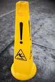 Caution wet floor, yellow warning sign. Stands on gray asphalt urban ground Stock Photography