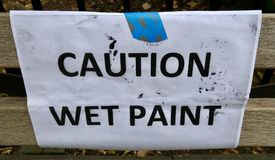 CAUTION: WET PAINT sign is taped onto a park bench. A white piece of paper warns people not to sit down on a recently painted bench stock photos