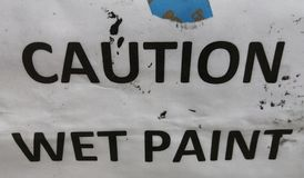 CAUTION WET PAINT is a sign on white paper white splatters of black paint Stock Image