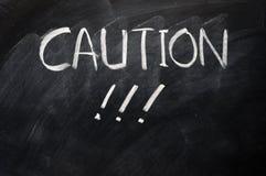 Caution written on blackboard Stock Image