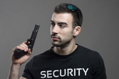 Cautious alerted security guard holding gun looking back over shoulder. Atmospheric contrasty portrait over gray studio background Stock Photography