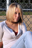 Cautious Blond Woman. Serious young blond woman with a cautious expression, sitting in front of a chain link fence and baseball field Stock Images