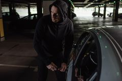 Cautious male robber in black hoodie intruding car. By screwdriver royalty free stock photo