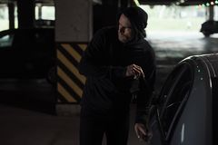 Cautious male thief in black hoodie intruding car. By picklock stock photos