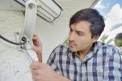 Cautious man installing security camera Stock Photos