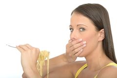 Cautious Natural Young Woman Holding A fork Full of Cooked Spaghetti Pasta Stock Photo