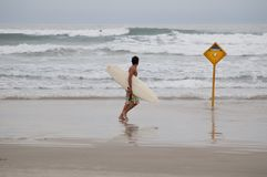 Cautious surfer moves away from dangerous spots. During overcast day Royalty Free Stock Images