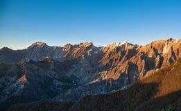 Cava di marmo nevosa del montagna di alpi di Apuane ed al tramonto nel winte Immagine Stock