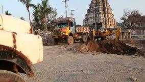 Cavador que cava lentamente la suciedad delante del templo Virupaksha almacen de metraje de vídeo