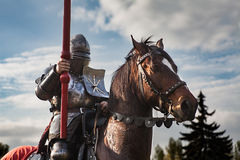 Cavaleiro a cavalo Cavalo na armadura com o cavaleiro que guarda a lança Cavalos no campo de batalha medieval Fotos de Stock Royalty Free
