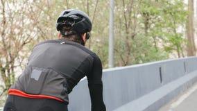 Cavaleiro da bicicleta que veste o equipamento preto e vermelho na bicicleta no parque Para trás perto siga acima o tiro Conceito video estoque