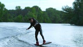 Cavaleiro da placa da vigília que salta altamente sobre a água Cavaleiro surfando da vigília na água video estoque