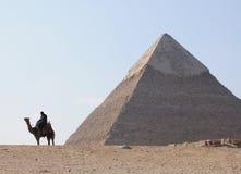 Cavaleiro do camelo por pirâmides Fotos de Stock Royalty Free