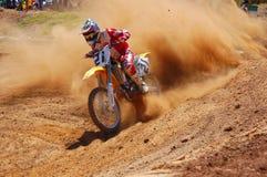 Cavaleiro do motocross que acelera fora do canto Imagens de Stock Royalty Free