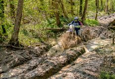 Cavaleiro do motocross que espirra a lama no terreno molhado e enlameado Competições abertas no motocross na província de Varese Imagem de Stock