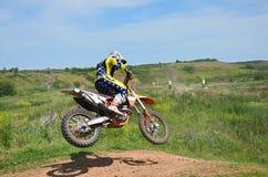 Cavaleiro do MX em terras de uma motocicleta espetacularmente Imagens de Stock