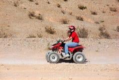 Cavaleiro do quadrilátero ATV no deserto Foto de Stock