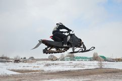 Cavaleiro do Snowmobile que voa o ar elevado imagens de stock