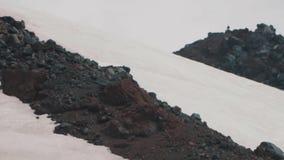 Cavaleiro extremo com o snowboard que escala na montanha para a construção de pedra vídeos de arquivo