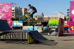 Cavaleiro extremo de BMX no capacete no skatepark na competição Imagens de Stock