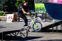 Cavaleiro extremo de BMX no capacete no skatepark na competição Imagens de Stock Royalty Free