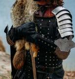 Cavaleiro medieval com a espada na armadura nos forestholds a espada um homem na armadura, com um casaco do lobo jogos do traje foto de stock