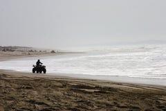 Cavaleiro mostrado em silhueta de ATV na praia Imagem de Stock Royalty Free