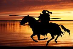 Cavaleiro preto e por do sol Imagens de Stock