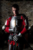 Cavaleiro Standing With Head curvado na oração e em guardar a espada do metal contra a parede de pedra velha Fotografia de Stock
