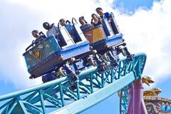 Cavaleiros com caras felizes e caras do pânico no roller coaster da praga da cobra de surpresa em jardins de Bush fotografia de stock royalty free