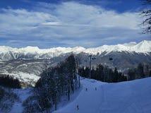 Cavaleiros do esqui e do snowboard nas montanhas Fotografia de Stock