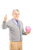 Cavalheiro maduro de sorriso que guarda um mealheiro e a doação do polegar u imagem de stock royalty free