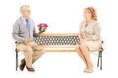 Cavalheiro maduro que dá um ramalhete da flor a uma mulher e a um assento fotos de stock royalty free