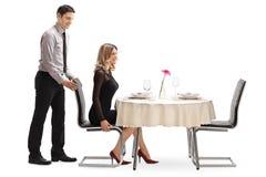 Cavalheiro que ajuda sua amiga com a cadeira imagens de stock royalty free
