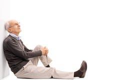 Cavalheiro superior alegre que senta-se no assoalho imagens de stock royalty free