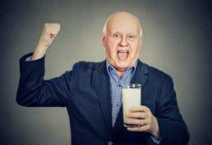 Cavalheiro superior entusiasmado que guarda um vidro do leite fotos de stock royalty free