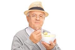 Cavalheiro superior que come o cereal de uma bacia Imagem de Stock Royalty Free