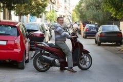Homme supérieur de sourire sur une motocyclette Photos stock