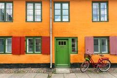 Cavalier de attente de bicyclette femelle près des murs jaunes du bâtiment historique dans le style traditionnel de Copenhague, D photo stock