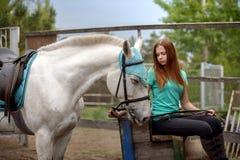 Cavalier de fille et son cheval à reposer près de l'écurie après la monte Image stock