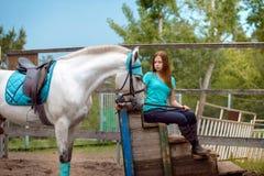 Cavalier de fille et son cheval à reposer près de l'écurie après la monte Photos stock