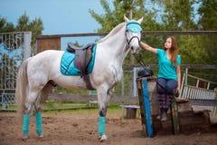 Cavalier de fille et son cheval à reposer près de l'écurie après la monte Images libres de droits