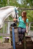 Cavalier de fille et son cheval à reposer près de l'écurie après la monte Photo stock
